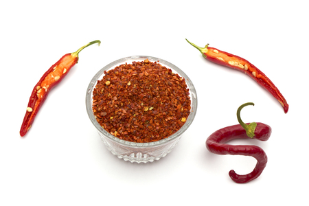 pepper flakes: Crushed red chili pepper in glass bowl from top on white background. Stock Photo