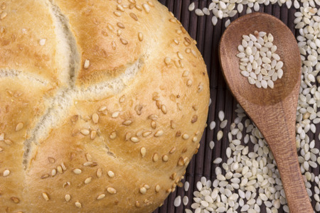 sesame seeds: Sesame bread with organic natural sesame seeds on wooden spoon. Stock Photo