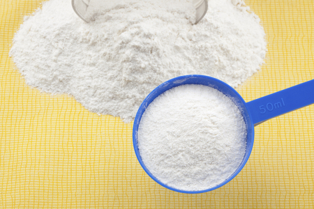 whey: Scoop of whey protein powder and shallow depth of field. Stock Photo