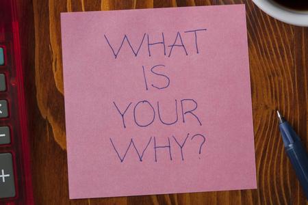 Qual è il tuo perché scritto su una nota su fondo in legno con penna. Archivio Fotografico