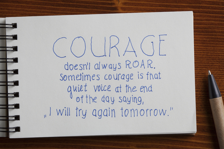 courage: Recycled paper notebook with tex courage on wooden background.