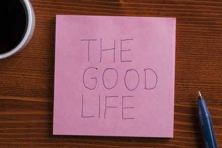 the good life: The good life handwritten on a note on wooden background with pen.