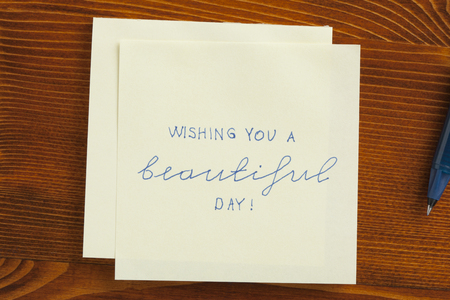 better days: Top view of wishing you a beautiful day note on the wooden desk with pen aside. Stock Photo
