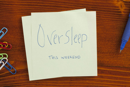 oversleep: Top view of Oversleep this weekend note on the wooden desk with pen aside. Stock Photo