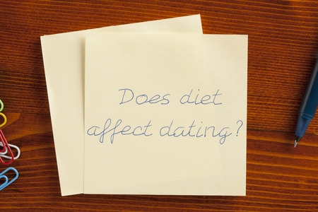 affect: Top view of Does diet affect dating note on the wooden desk with pen aside.