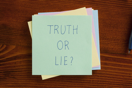 Top view of truth or lie written note on the wooden desk with pen aside. Stock Photo