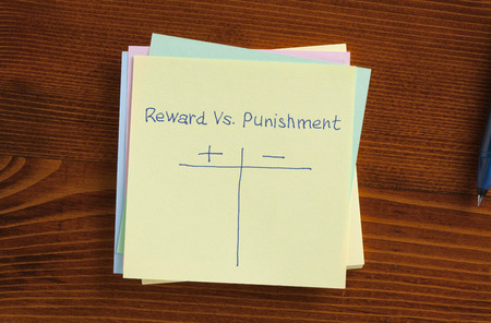 vs: Top view of reward vs punishment written note on the wooden desk with pen aside.