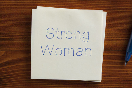challenging sex: Top view of Strong Woman written note on the wooden desk with pen aside.