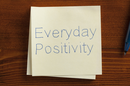 positiveness: Top view of Everyday Positivity written note on the wooden desk with pen aside.