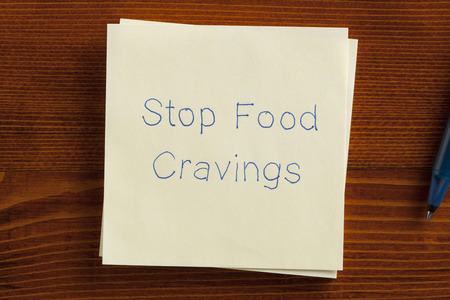 cravings: Top view of Stop Food Cravings written note on the wooden desk with pen aside.