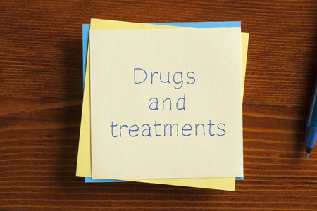 memory drugs: Top view of Drugs and treatments written note on the wooden desk with pen aside.