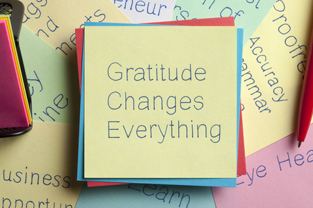 humility: Top view of Gratitude Changes Everything written on a note with a pen aside.