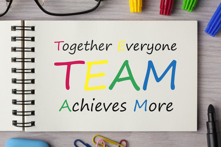 TEAM - Together Everyone Achieves More in notebook on wooden desk with marker pen and glasses. Top view. Foto de archivo