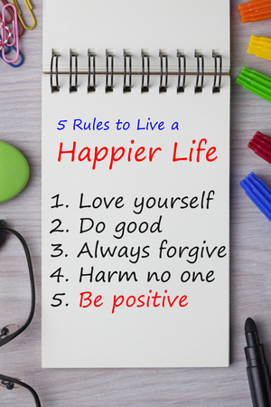 Rules to Live a Happier Life written in notebook on wooden desk with marker pen and glasses. Top view. Standard-Bild