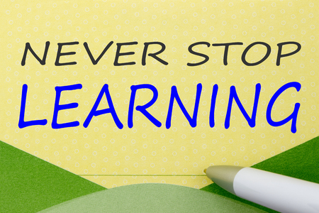 NEVER STOP LEARNING written on a yellow note.Top view.
