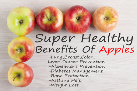 Frame of apples with textSuper Healthy Benefits Of Appleson wooden surface. Top view.