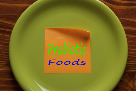 Probiotic Foods written in note on the green plate.Top view. Standard-Bild