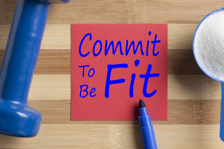 Commit To Be Fit written on note with sport supplement and dumbbell on wooden desk. Top view.