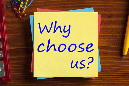 Why choose us? written on note with pen and calculator on wooden desk. Top view.