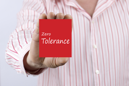 Male hand showing card with text Zero Tolerance message.Defocused chart background.