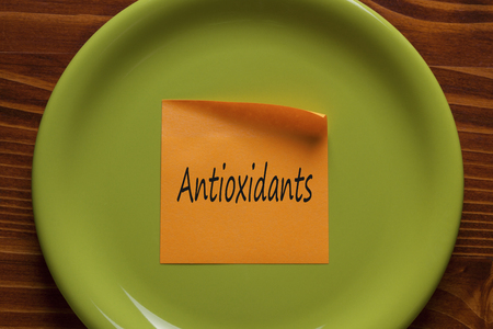 Antioxidants written in note on the green plate.Top view. 스톡 콘텐츠