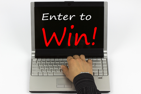 Enter to Win! written on laptop screen.Hand of a man on a keyboard. Standard-Bild
