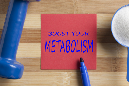 Boost Your Metabolism written in note with marker pen, sport supplement and dumbbell on wooden.Top view.