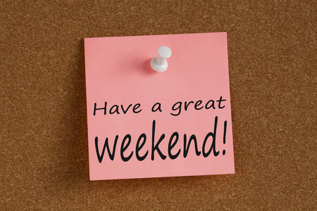 Have a great weekend written on remember note with pin on cork board.