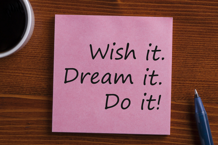 Dream it, Wish it, Do it! written in note with pen and cup of coffee on wooden desk. Top view.