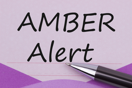 AMBER Alert written on purple note paper and pen.Top view. Standard-Bild
