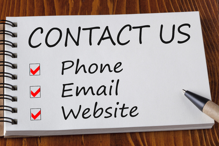 Contact us by phone, email or website check boxes written in notebook on wooden desk. Standard-Bild