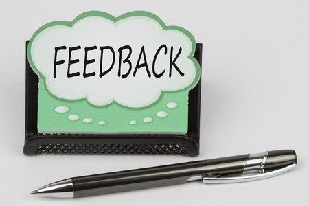 FEEDBACK written in speech bubble with pen on a white background.