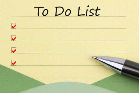 To Do List written on yellow note paper and pen.Top view.