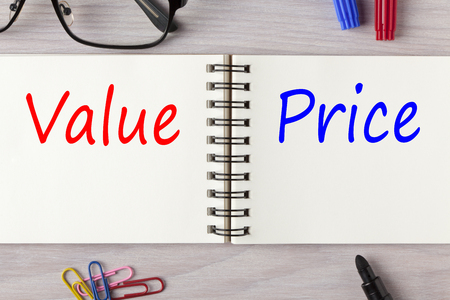 Value and Price written in notebook on wooden desk with marker pen and glasses. Top view. Standard-Bild