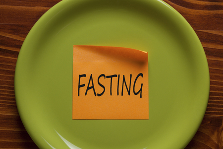 FASTING written in orange sticky note on the green plate.Business concept.Top view.