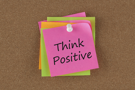 Think Positive written in remember note pinned on a cork board.Business concept.