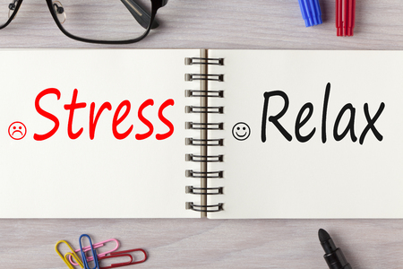 Stress or Relax written on notebook on wooden desk with marker pen and glasses. Business concept. Standard-Bild