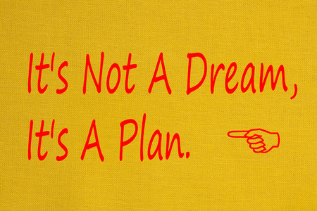 Its Not A Dream Its A Plan written on yellow fabric textile texture.Business concept.Top view.