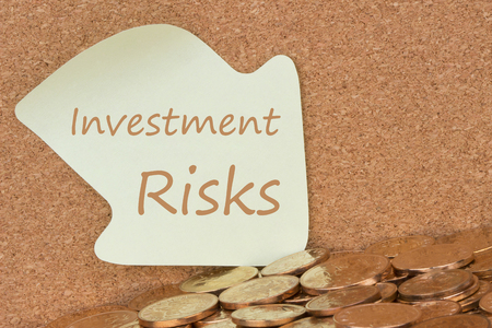 Investment Risks written reminder note and many of gold coins. Defocused chart background.