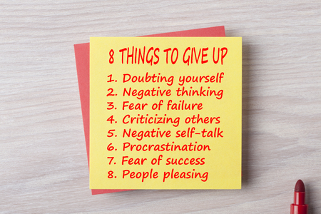 8 Things To Give Up written on note with marker pen on wooden desk.Creative Inspiring Motivation Quote Concept Stok Fotoğraf