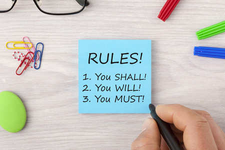 Hand writing RULES! You SHALL! You WILL! You MUST! in note with marker pen and glasses on wooden desk. Business Concept. Top view.