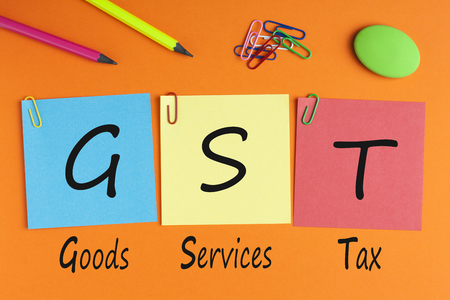 Goods Services Tax words with GST written on color notes with and office supplies. Business Concept. Top view.