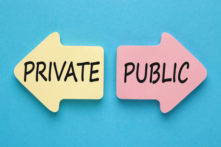 PRIVATE and PUBLIC written in paper arrows on blue background. Business concept.  Фото со стока