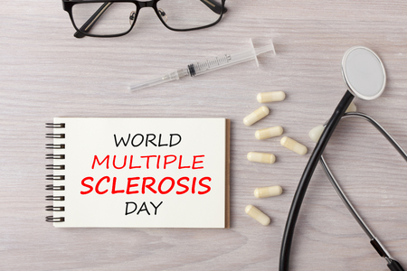 World Multiple Sclerosis (MS) Day written on notebook with stethoscope, syringe, eyeglasses and pills on wooden desk. Medical concept.
