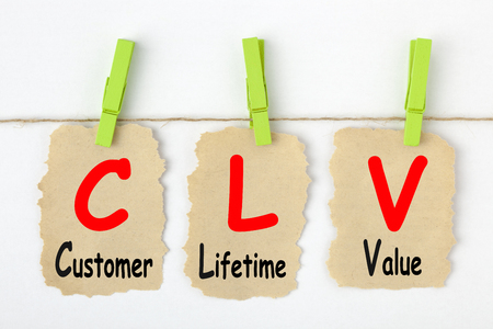 Customer Lifetime Value- CLV writen on old torn paper with clip hanging. Acronym business concept.