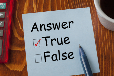 True or False written in note with pen, calculator and cup of coffee on wooden desk. Business concept.