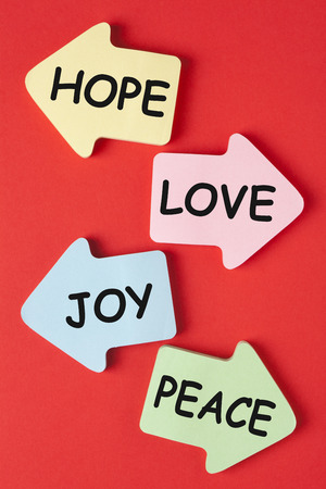 HOPE, LOVE, JOY and PEACE written on arrows on red background. Stock Photo