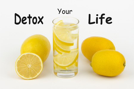 Detox Your Life written on white background and glass of water with lemon slices.