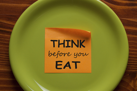 Think Before You Eat written on sticky note on the green plate. Health Tip. Stockfoto