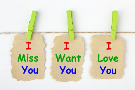 I Miss You, I Want You, I Love You written on old torn paper with clip hanging.